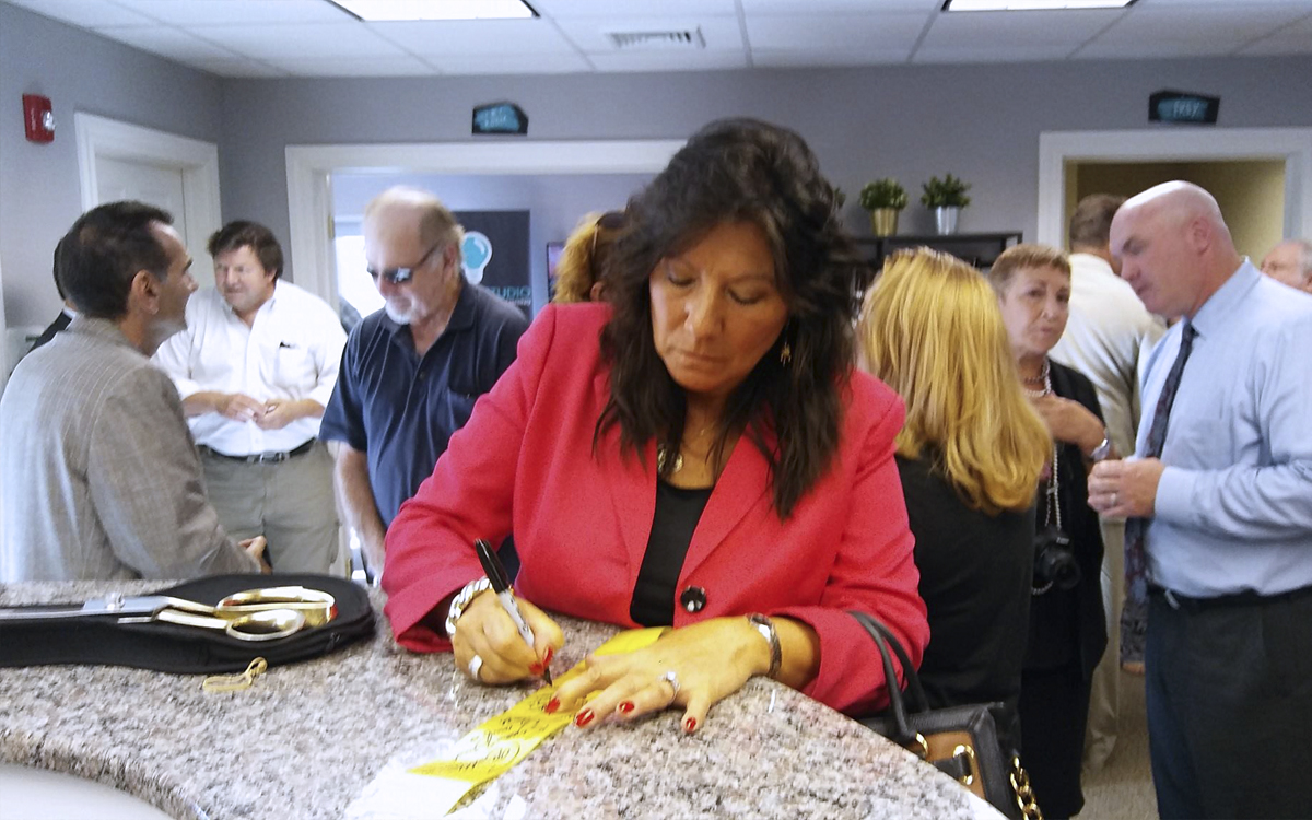 Senator Sue Serino signing the ribbon at the open house for Content Studio at Martinelli Custom Publishing.